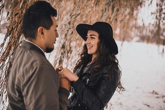 멕시코 남자는 겨울에 자연에 검은 가죽 재킷과 검은 모자에 우크라이나 여자의 손을 보유하고