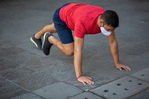 フェイスマスクを身に着けて屋外でトレーニングするメキシコ人男性、新しい通常