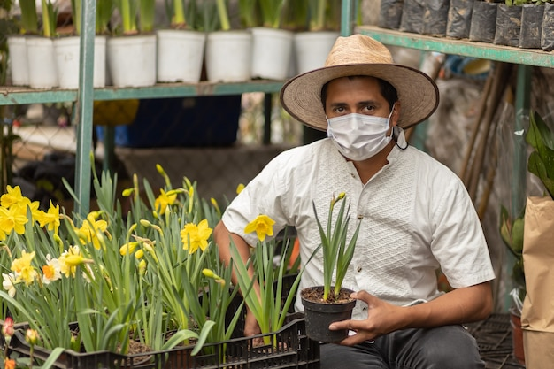 Mexican man working in nursery wearing face mask, new normal