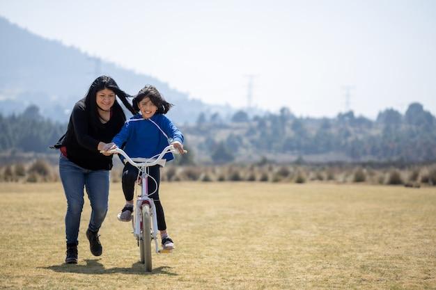 자전거를 타고 딸을 가르치는 멕시코 어머니