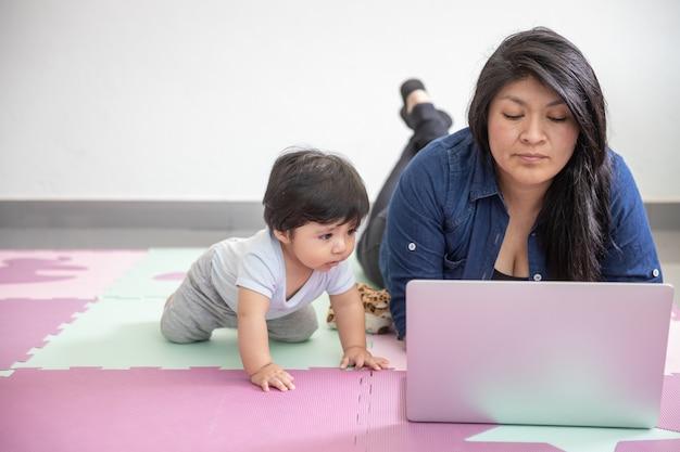 家で床に敷設し、息子と遊ぶメキシコの母