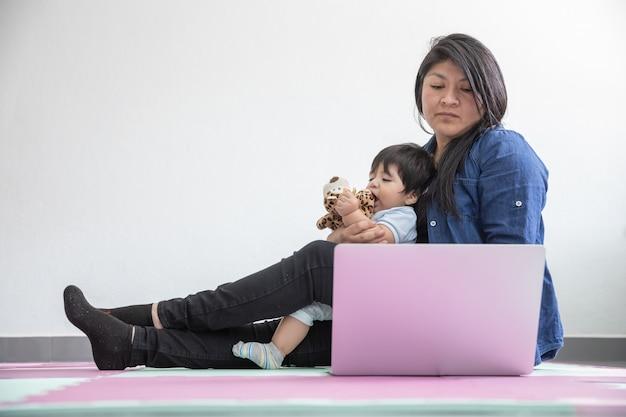 Мексиканская мать, работающая из дома, лежащая на полу и играющая с сыном