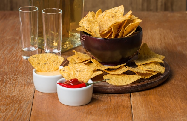 Mexican nacho chips, cheese and salsa dip in bowl