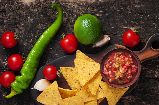Mexican nacho chips and salsa dip in bowl on wooden