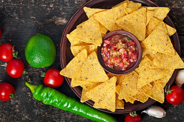 Mexican nacho chips and salsa dip in  bowl