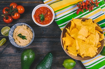 Mexican nachos chips; avocado; salsa sauce; cherry tomatoes; red chilies and lemon on wooden table