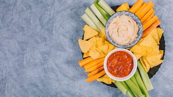 Mexican nachos chips; slices of carrot with celery stem in tray with salsa sauce in bowl on cement background