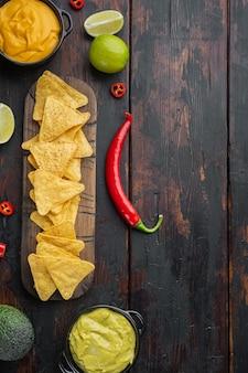 古い木製のテーブルの上に、チーズとワカモレソースを添えたメキシコのナチョスチップス