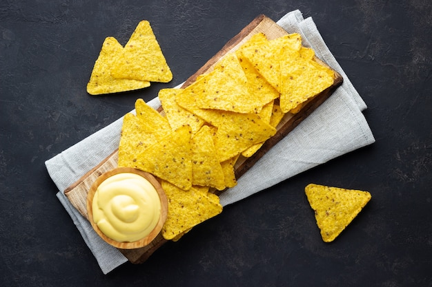Mexican nachos chips over wooden rustic board with cheese sauce on dark background.