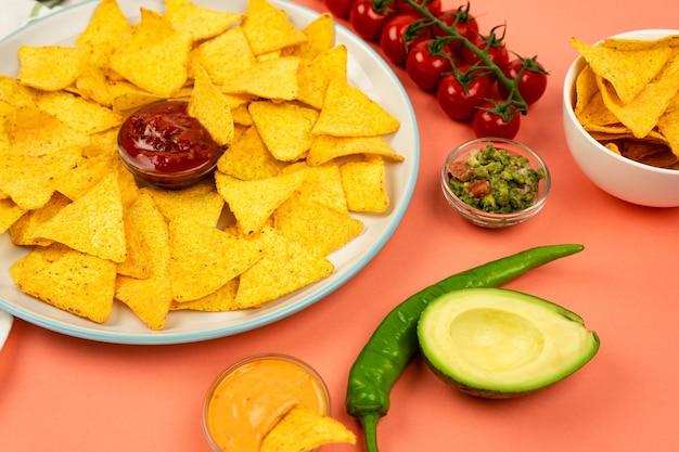 メキシカンナチョスのコーンチップスをソースと野菜のプレートに乗せたもの。おいしいメキシコ料理。