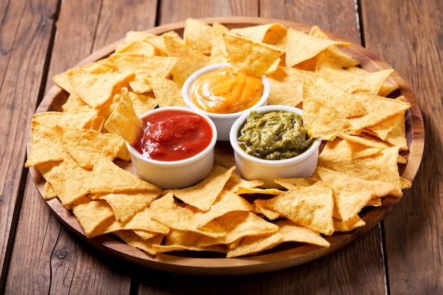 ワカモレ、サルサ、チーズのメキシコのナチョスコーンチップスを木製のテーブルに浸します