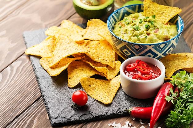メキシコのナチョス、ワカモレとホットトマトソースのトルティーヤチップスを木の表面に