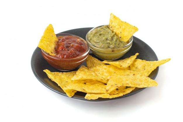 Мексиканские чипсы из тортильи начос с гуакамоле и сальсой в темной тарелке. изолированные на белом фоне