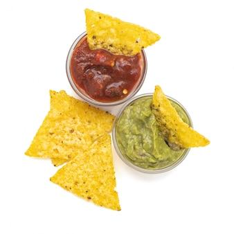 Мексиканские чипсы из тортильи начос с гуакамоле и сальсой. изолированные на белом фоне. вид сверху