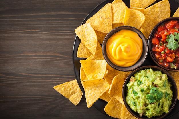 아보카도 소스, 살사 및 치즈 딥 멕시코 나 초 옥수수 칩 프리미엄 사진