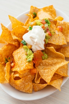 Mexican nachos tortilla chips with jalapeno, guacamole, tomatoes salsa and dip