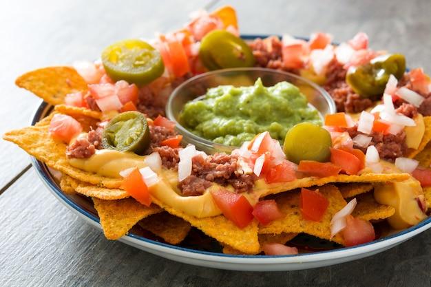 나무 테이블에 접시에 쇠고기, 아보카도 소스, 치즈 소스, 고추, 토마토, 양파와 함께 멕시코 나쵸