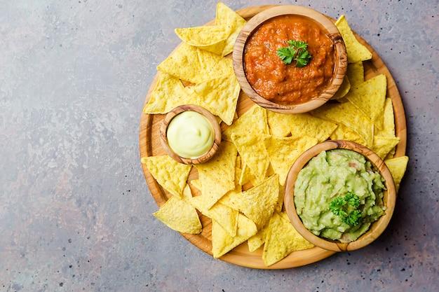 Мексиканские начо с гуакамоле, сальсой и сырным соусом в деревянных мисках на темной поверхности, вид сверху.