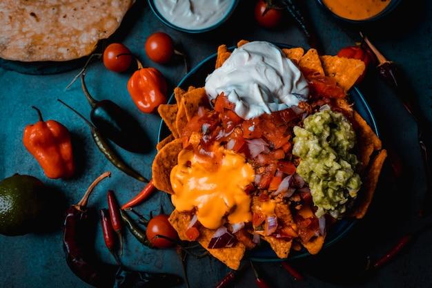 ワカモレのサワークリームとチェダーチーズのスパイシーなピコデガロを添えたメキシコのナチョス