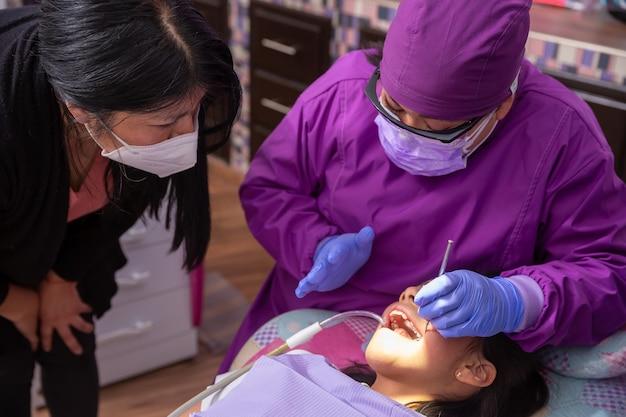 若い患者とその母親に説明するメキシコの小児歯科医