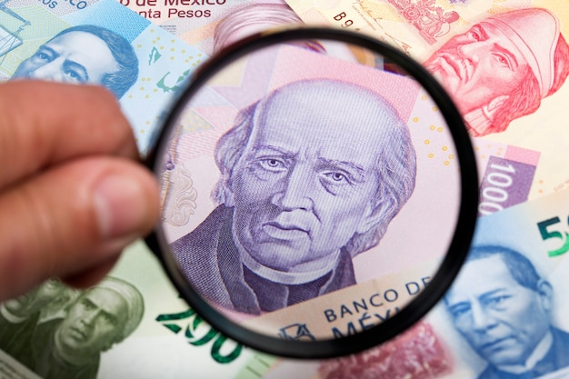 Mexican pesos in a magnifying glass background