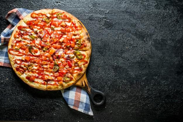 黒の素朴なテーブルにナプキンとメキシコのピザ