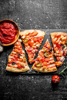 그릇에 로즈마리와 토마토 페이스트와 멕시코 피자. 어두운 소박한 배경에