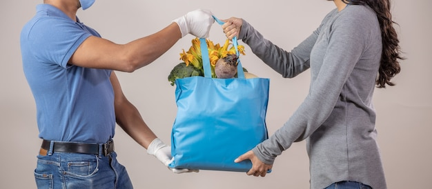 Mexican protected delivery man delivering ecological bag with fruits and vegetables to woman