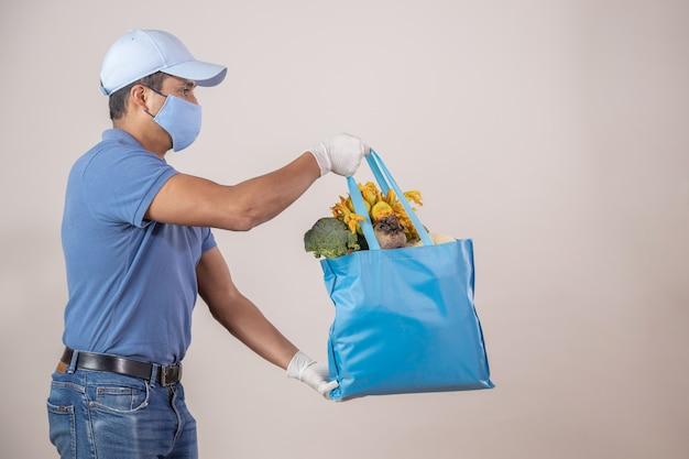 メキシコの果物と野菜の生態学的なバッグを持つ配達人