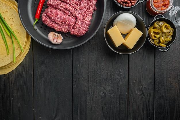 Мексиканская кесадилья и ингредиенты, на черном деревянном столе с копией пространства для текста