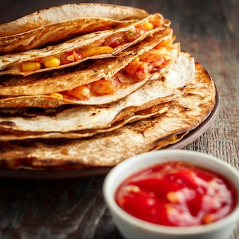 Mexican quesadilla and salsa on a wooden table