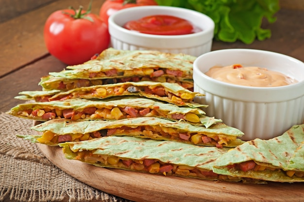 Mexican quesadilla sliced with vegetables and sauces on the table