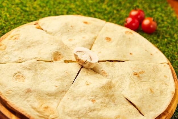 緑の草の上にチキン、チーズ、マッシュルームを添えたメキシコのケサディーヤ