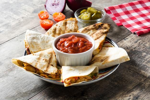Мексиканская кесадилья с курицей, сыром и перцем на деревянном столе