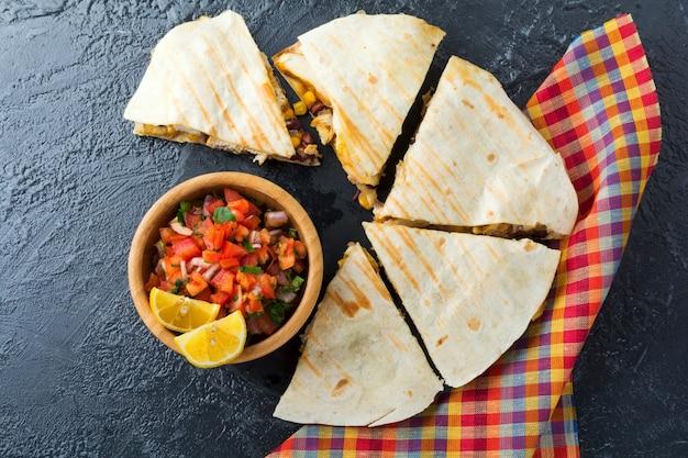 Мексиканская кесадилья с курицей, кукурузой, красной фасолью, сыром, перцем и сальсой. выборочный фокус. вид сверху.
