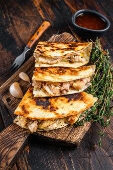 木製のまな板にチキン、パプリカ、チーズ、コリアンダーを添えたメキシコのケサディーヤ。暗い木製の背景。上面図。