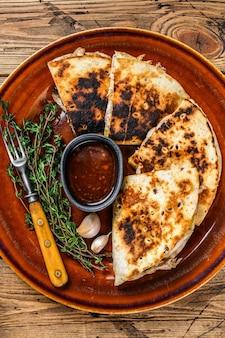 Мексиканская кесадилья с курицей, паприкой, сыром и кинзой на деревянной разделочной доске на деревянном столе. вид сверху.