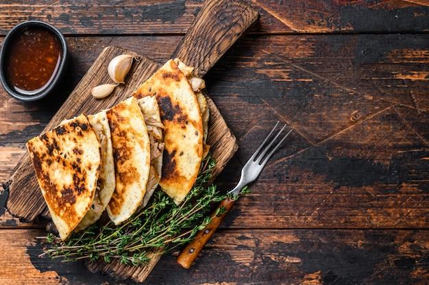 나무 커팅 보드에 닭고기, 파프리카, 치즈, 고수와 멕시코 퀘사 디아