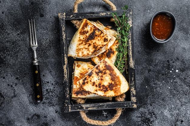 チキン、トマト、コーン、チーズを添えたメキシコのケサディーヤ。黒の背景。上面図。