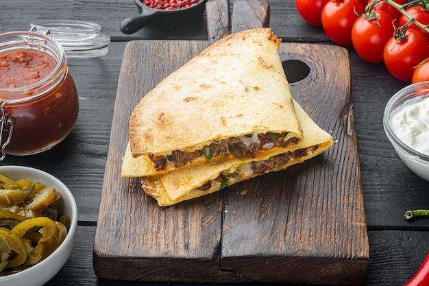 黒い木製のテーブルの背景に、チキントマトコーンチーズミックスとメキシコのケサディーヤ