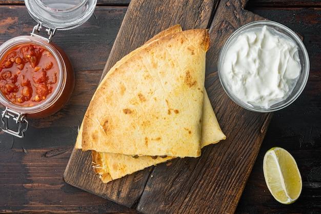 古い暗い木製のテーブルの上に、チキントマトコーンチーズミックスとメキシコのケサディーヤ