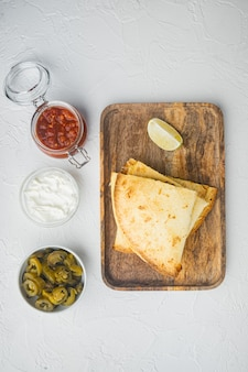 Mexican quesadilla wrap with chicken, corn and sweet pepper and salsa sauce, on white background, top view flat lay