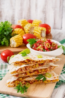 Mexican quesadilla wrap with chicken, corn and sweet pepper and salsa