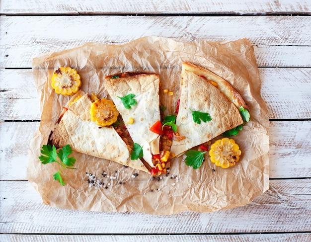 メキシコのケサディーヤは、羊皮紙とテーブルの上に野菜、トウモロコシ、ピーマン、ソースで包みます。水平方向のビュー。
