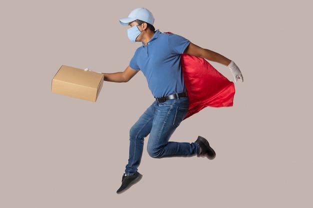コロナウイルスのパンデミックと手袋をはめて飛んでいるグローブのためにフェイスマスクを着用しているメキシコの赤い帽子の宅配便