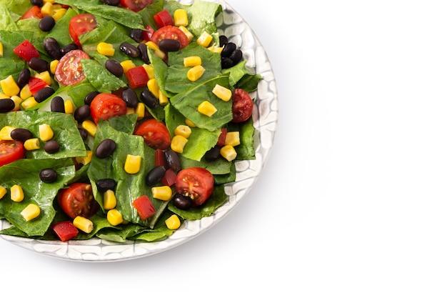 黒豆、トウモロコシ、トマト、レタス、コショウを白で分離したメキシカンサラダ