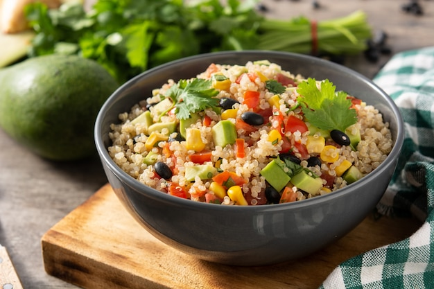 Mexican salad with quinoa in bowl on wooden table