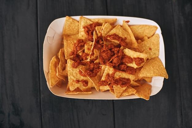 Мексиканские закуски. блюдо мексиканской кухни начос кон карне. концепция мексиканской кухни. вид сверху, деревянный фон