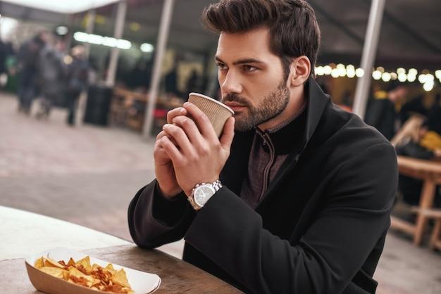 커피와 함께 하는 멕시칸 스낵. 외로운 청년이 멕시코 음식 접시 근처에 앉아 커피를 마시고 있습니다. 멕시코 요리의 개념입니다. 측면 보기, 흐린 배경
