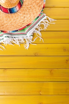 Mexican sombrero and traditional serape blanket laid on a yellow painted pine wood floor.